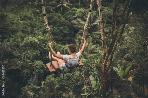 Poster Kaki Young tourist woman swinging on the cliff in the jungle rainforest of a tropical Bali island.