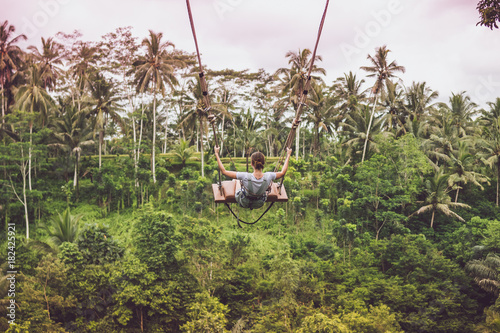 Foto op Aluminium Bali Young tourist woman swinging on the cliff in the jungle rainforest of a tropical Bali island.