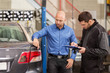 mechanic and customer looking at car taillight
