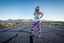 Blonde Female Wearing Sunglasses And A Patriotic Fourth Of July Outfit Stand In The Middle Of A Road In California During Sunset