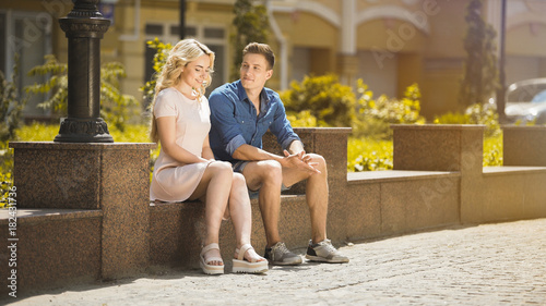 Male and female sitting on bench next to each other, feeling awkward, first date Canvas Print