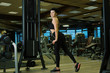 Athletic woman workout out squats weighted lunges exercise with suspension straps in fitness club or gym