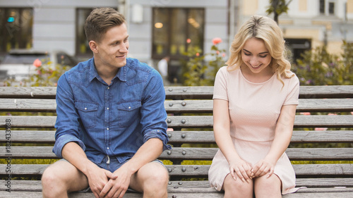Shy blonde girl smiling, attractive guy flirting with beautiful woman on bench Fototapet