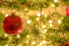 Beautiful Christmas Background - Red Bauble On A Background Of Blurred Lights On A Christmas Tree With Bokeh Effect.