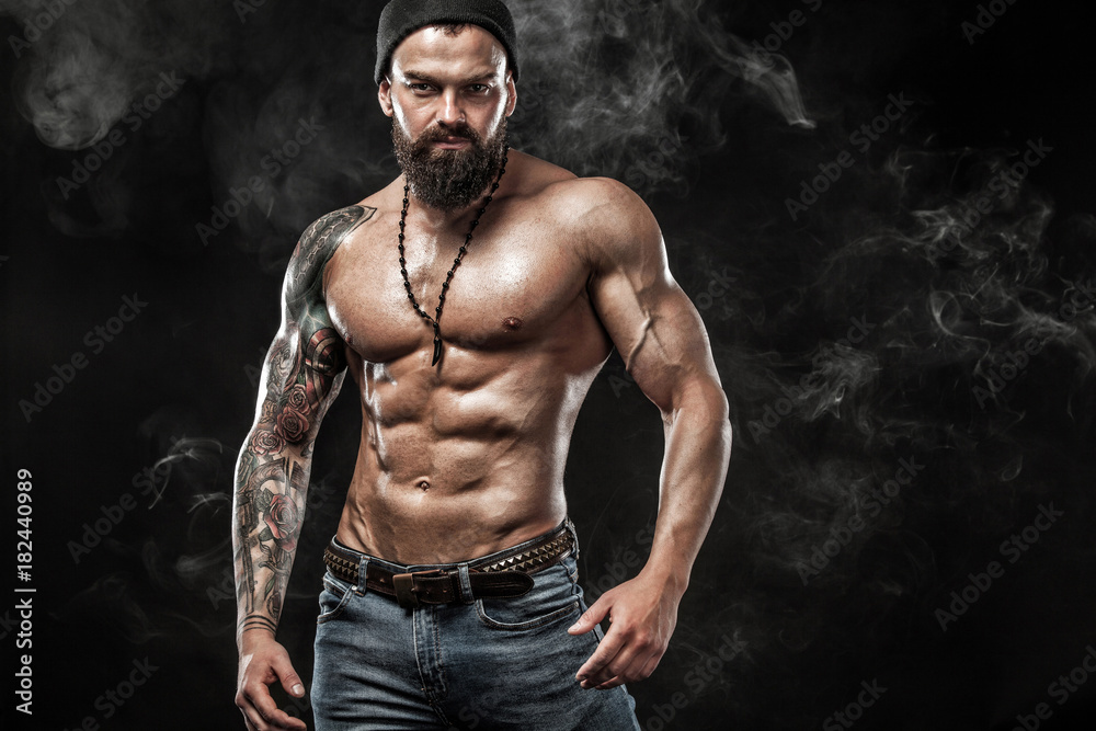 Fototapeta Handsome fit man posing wearing in jeans with tattoo. Sport and fashion concept isolated on black background.