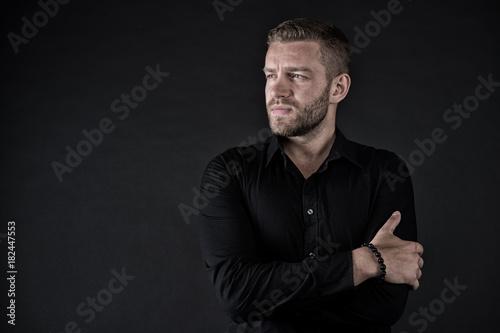 Fotografie, Obraz  Macho in black shirt pose with folded hands