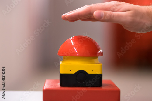 Poster Macarons Hand above a red emergency button