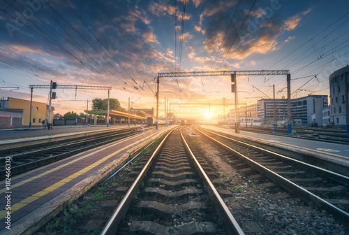 Foto auf AluDibond Bahnhof Railway station and beautiful colorful sky at sunset. Industrial landscape with railroad, blue sky with red and orange clouds in dusk. Railway junction in the evening. Railway platfform.Transportation