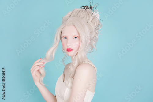 Fototapeta  Blonde woman with beautiful luxurious rococo hair style in white dress on a blue