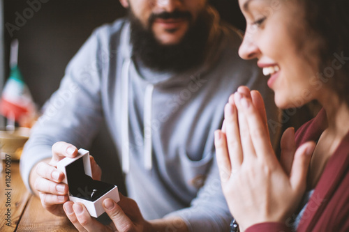 Fotografía A man with a beard asks to marry his happy and surprised girl in a cafe, gives a diamond ring