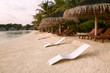 Beach chairs under straw umbrellas. Indian ocean coastline on Maldives island. White sandy beach and calm sea. Travel and vacation concept.