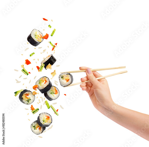 Falling pieces of sushi and sushi roll with wooden chopsticks in female hand