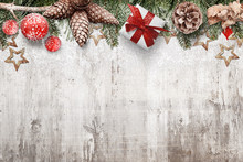 Christmas Background With Pine Cones, Fir Branches, Ornaments And Gifts Covered With Snow. Old White Wooden Desk With Christmas Decorations Above, Free Space For Text