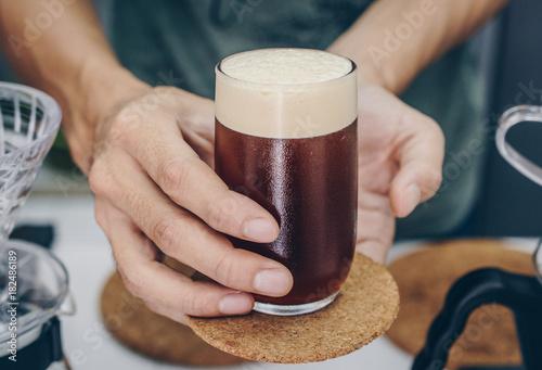Fotografia Barista holding and serving nitro cold brew coffee.