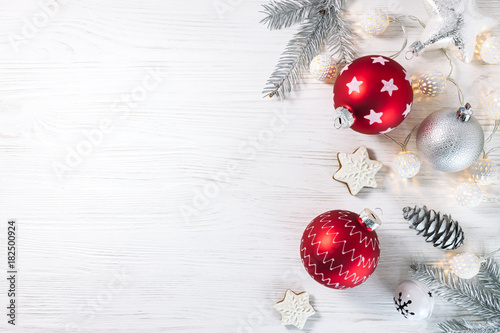 christmas glass balls with gingerbread cookies and garland on white wooden background flat view