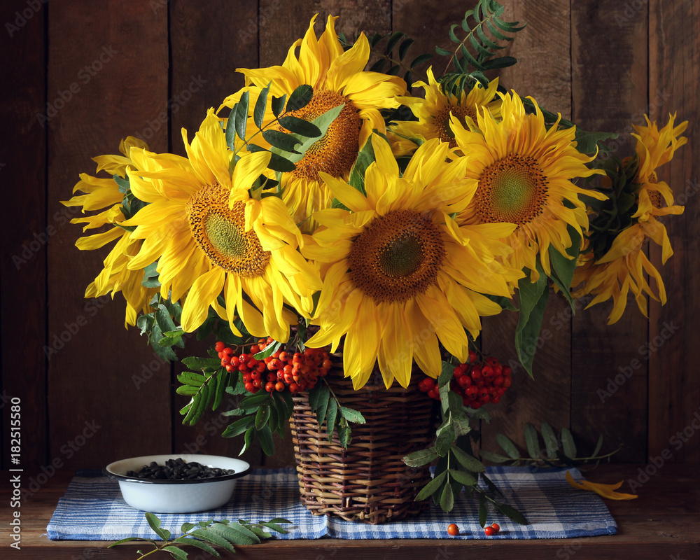 Beautiful bouquet of sunflowers and Rowan branches with berries in the basket.