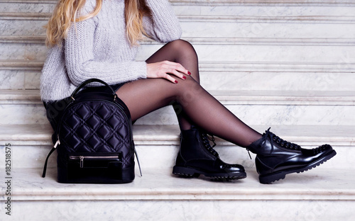 Woman legs in black ankle boots with bag.