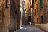 Fototapeta Uliczki - Beautiful medieval narrow street in the spring, Siena, Italy. Historic centre of Siena has been declared by UNESCO a World Heritage Site.