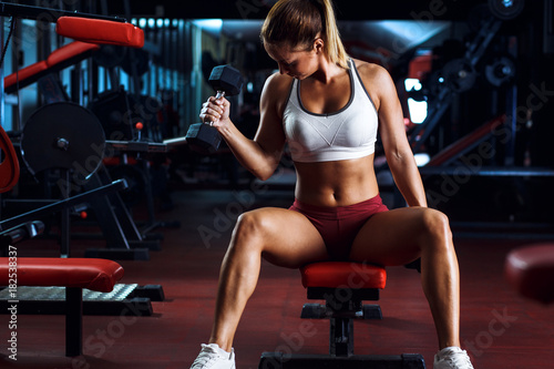 Spoed Foto op Canvas Fitness Young woman exercising with weight in the gym.