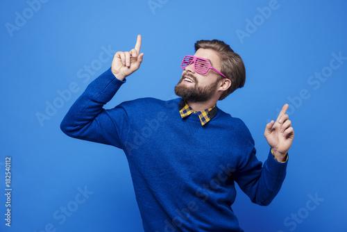 Man with sunglasses dancing at studio shot