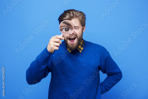 Funny man watching his eyeball in the magnifying glass . Fototapet