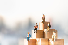 Miniature People: Small Businessmen Sitting On Wooden Blocks Step, Money, Financial, Business Growth Concept.