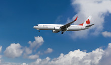 Commercial Airplane With Canadian Flag On The Tail And Fuselage Landing Or Taking Off From The Airport With Blue Cloudy Sky In The Background