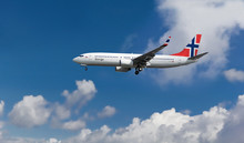 Commercial Airplane With Norwegian Flag On The Tail And Fuselage Landing Or Taking Off From The Airport With Blue Cloudy Sky In The Background