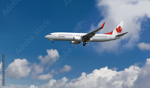 Fényképezés  Commercial airplane with Canadian flag on the tail and fuselage landing or takin