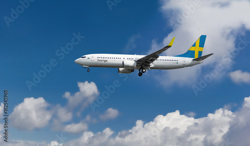 Fotografia  Commercial airplane with flag of Sweden on the tail and fuselage landing or taki