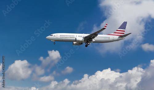 Fotografia  Commercial airplane with American flag on the tail and fuselage landing or takin