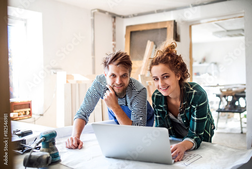 Obraz Young couple with laptop in the carpenter workroom. - fototapety do salonu