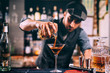 canvas print picture - Barman creating signature drink at bar counter. Bitter whisey with beer cocktail