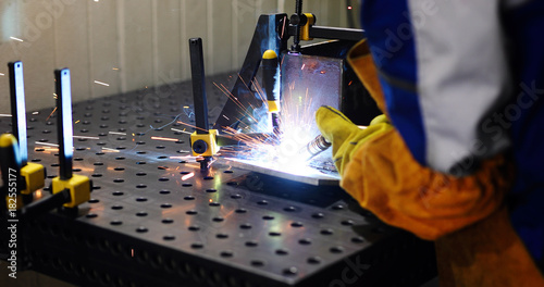 Staande foto Industrial geb. man welds at the factory working in metal industry