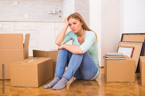 Tired woman sitting on the floor while moving into new home. - Buy ...
