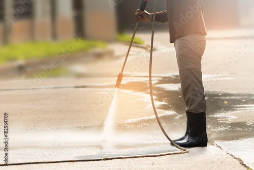 High pressure deep cleaning.Worker cleaning driveway with gasoline high pressure washer ,professional cleaning services. #182564709
