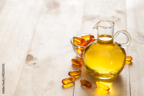 Fototapeta Fish oil in a jug and capsules on wooden texture and table obraz