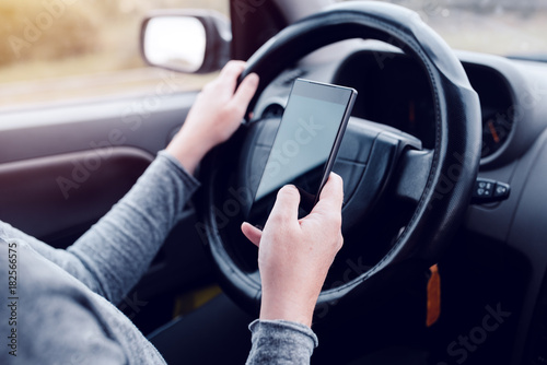 Fotografie, Obraz Woman simultaneously driving car and reading text message