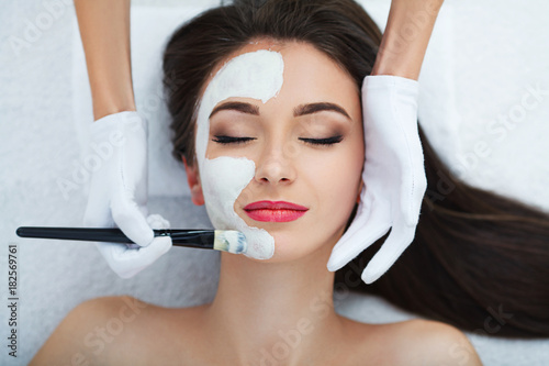 Facial Skin Care. Beautiful Woman Getting Cosmetic Mask In Salon