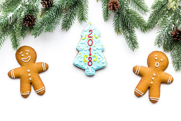 Cookies for New Year. Gingerbread man and spruce with lettering 2018 near spruce branch on white background top view copyspace