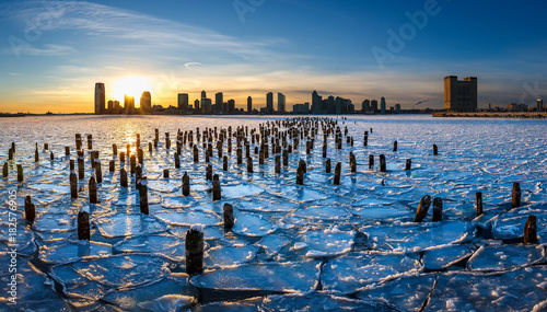 Fotografie, Tablou  Sunset on the frozen Hudson River with old wood pilings and view on Downtown Jer
