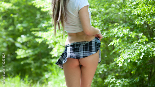 Valokuva  Sexy young girl in a short skirt flirts in a summer park