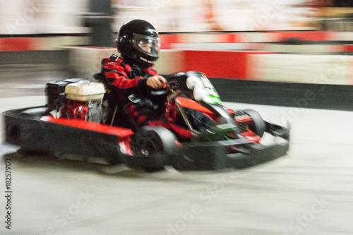 Fotografiet  Cart (kart) blurred by high speed, a boy having fun - driving fast, racing, speeding