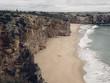 Felsküstenstreifen mit isoliertem Strand und einem kleinen Dorf in der Ferne