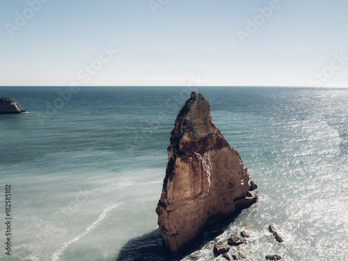 Big rock sitting in the blue ocean on a sunny day