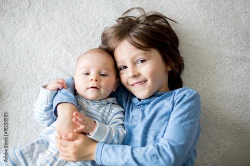 Obraz na plátne Happy brothers, baby and preschool children, hugging at home on white blanket