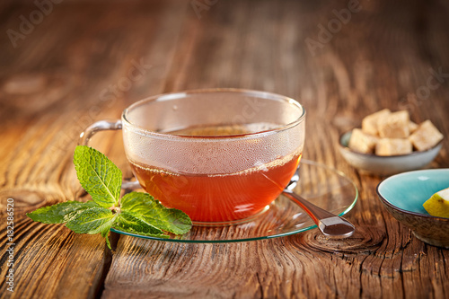 Staande foto Thee Hot tea in glass teacup with mitn and brown sugar cubes