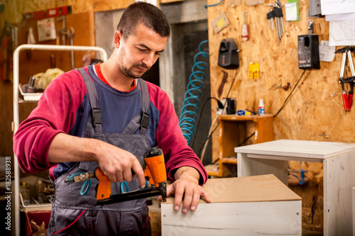 Fototapeta Man builds furniture in the carpentry shop obraz na płótnie