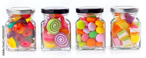 Foto op Aluminium Snoepjes colorful candies in glass jars on white background - Web banner with food concept