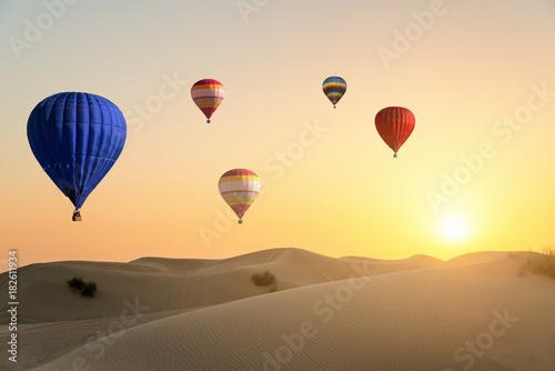 Air ballons flying over desert at sunset